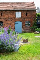 Old brick house in cottage garden with green lawn
