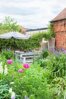 Blooming cottage garden with seating area next to brick barn
