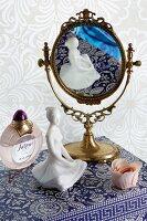 Feminine still-life arrangement of mirror, china figurine and perfume