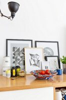 Graphical artworks leaning against wall behind kitchen utensils