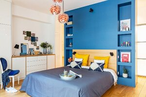 Bed against blue wall with integrated shelving on either side