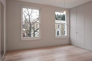 Corner of elegant room with minimalist, floor-to-ceiling fitted cupboards and parquet floor
