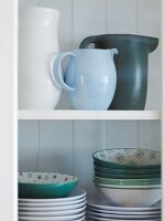 Various jugs, plates and bowls on a white wall shelf