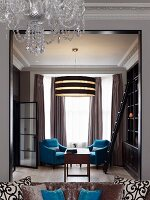 Elegant reading area in traditional interior with turquoise armchairs and modern pendant lamp