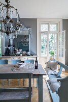 Grey-blue wooden benches around rustic table below vintage-style chandelier in dining room