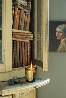 Antiquarian books in open cabinet and lit tealight next to oil painting