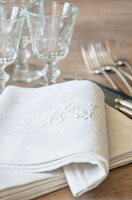 Elegant linen napkin with embroidered initials in front of wine glasses and silver cutlery