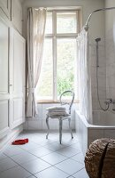 White, diagonal floor tiles, fitted cupboard and antique chair below window in renovated bathroom