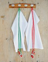 White tea towels decorated with strawberry-motif tags hanging from coloured ribbons