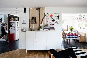 White sideboard between open doorways leading into dining room and kitchen in open-plan interior