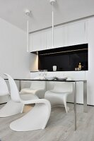 White classic shell chair around delicate table in front of kitchen units with black splashback