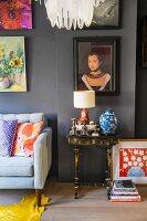 Side table in living room below artworks on grey wall