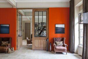 Zwei Sessel unter Bildern an orangener Wand vor einer Tür