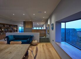 Open-plan designer interior of architect-designed house with panoramic window with sea view
