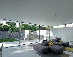 Designer sofa combination in lounge area with view of summery terrace and stone wall through glass wall