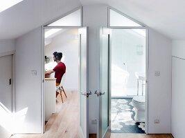 View into study and bathroom in bright attic interior