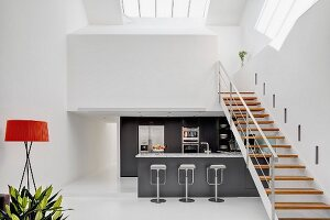 Steel staircase with wooden treads leading to white gallery level above charcoal-grey kitchen