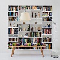 White bookcase in niche behind wooden bench and designer standard lamp