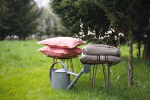 Woollen blankets, zinc watering can and cushions on stools on lawn