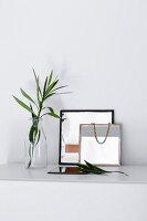 Zwei DIY-Spiegel neben Glasvase mit Blätterzweig