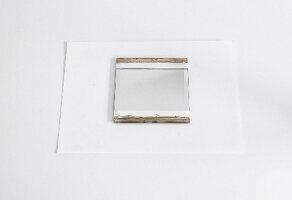 Spiegel mit Klebeband abgeklebt und bemalt auf weissem Papier