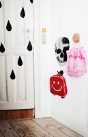 Children's bags on wall pegs next to skull mural and front door painted with pattern of black raindrops