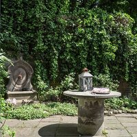Lantern and glass bowl of flowers on round concrete table in front of antique water spout on climber-covered garden wall