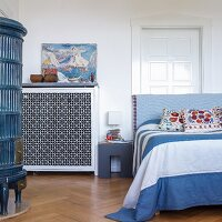 Wilhelmine-era tiled stove, bed with blue blanket and white panelled door in bedroom of period apartment