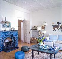 Blue-tiled open fireplace in Scandinavian living room