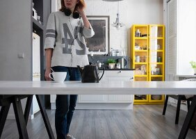 Woman wearing headphones standing next to teapot and teacup on kitchen table