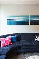 Triptych above blue corner sofa with colourful scatter cushions