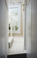 Narrow hallway in rustic house with white wooden floor and large mirror on wall in background