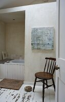 Wooden chair, partially visible bathtub and white, shabby-chic wooden floor in simple bathroom