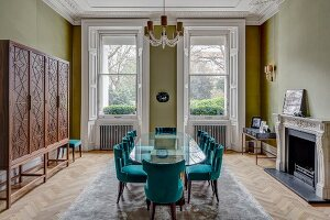 Oval glass table and petrol-blue upholstered chairs in grand dining room painted green