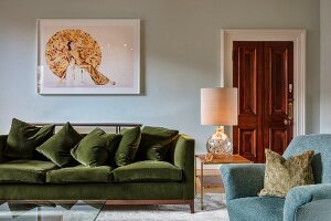 Green velvet sofa below picture on wall and table lamp on side table in elegant living area