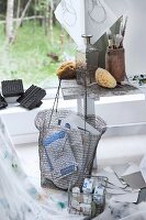 Art supplies in wire basket in front of paintbrushes and sponges on vintage wooden bank