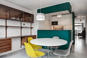 Classic yellow chairs around white table in front of petrol-blue kitchen counter and custom shelving made from exotic wood
