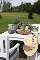 White wooden chairs and table on terrace with straw hat on backrest of chair