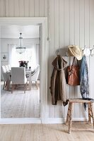 Rustic hallway with wall-mounted coat rack and dining area in background
