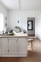 Kitchen counter with white base units in front of dining set in rustic interior with white wood-clad walls and cork flooring