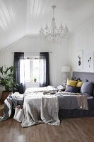 Blankets and cushions on box-spring bed with grey headboard in bedroom with white wood cladding