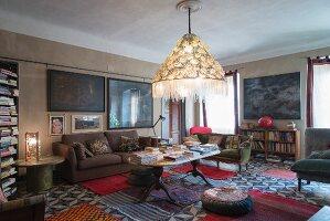 Beleuchteter Lampenschirm mit Fransen, Polstermöbel und verschiedene Teppiche auf Zementfliesen im Wohnzimmer