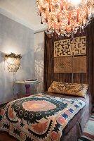 Bett mit Ethno Tagesdecke und Kissen, Leuchten mit Glasschmuck