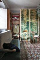 Zimmer mit Raumteiler, Bücherregal, grauem Polstersofa und gemustertem Zementfliesenboden