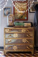 Antique finds on top of marquetry chest of drawers; glass pendants hanging from lampshade in foreground