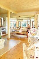 Offener Wohnraum mit heller Holzdecke, Korbmöbeln und Erker mit Mutter und Tochter am Essplatz
