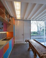 Colourful fitted kitchen with rustic workbench and view of bare trees through terrace doors