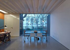 Dining table on castors in front of terrace windows and view of neighbouring building at twilight