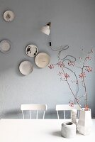 Arrangement of vases and branches of red berries in front of decorative plates and retro lamp on grey wall