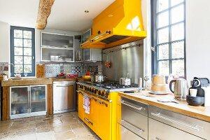Zeitgenössische Edelstahlküche mit gelbem Kochbereich